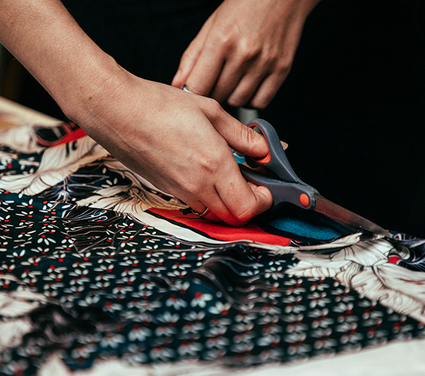 A woman hand is shown cutting into a printed black, white and red fabric using scissors
