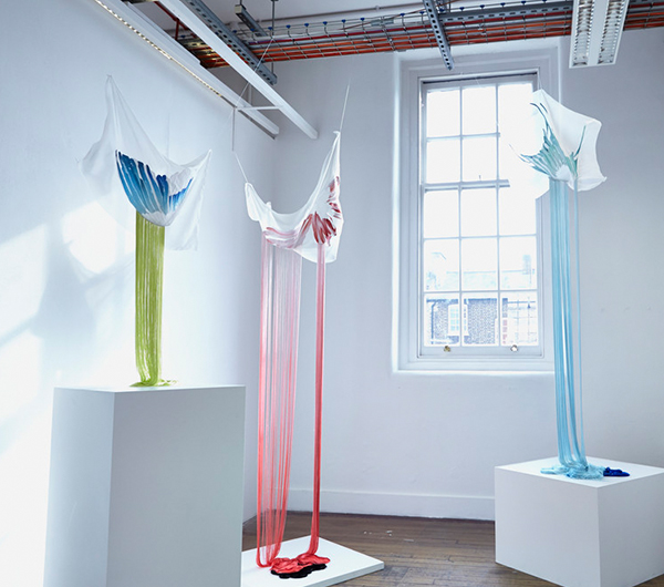 A collection of three textile pieces shown in a gallery space hung off the ceiling