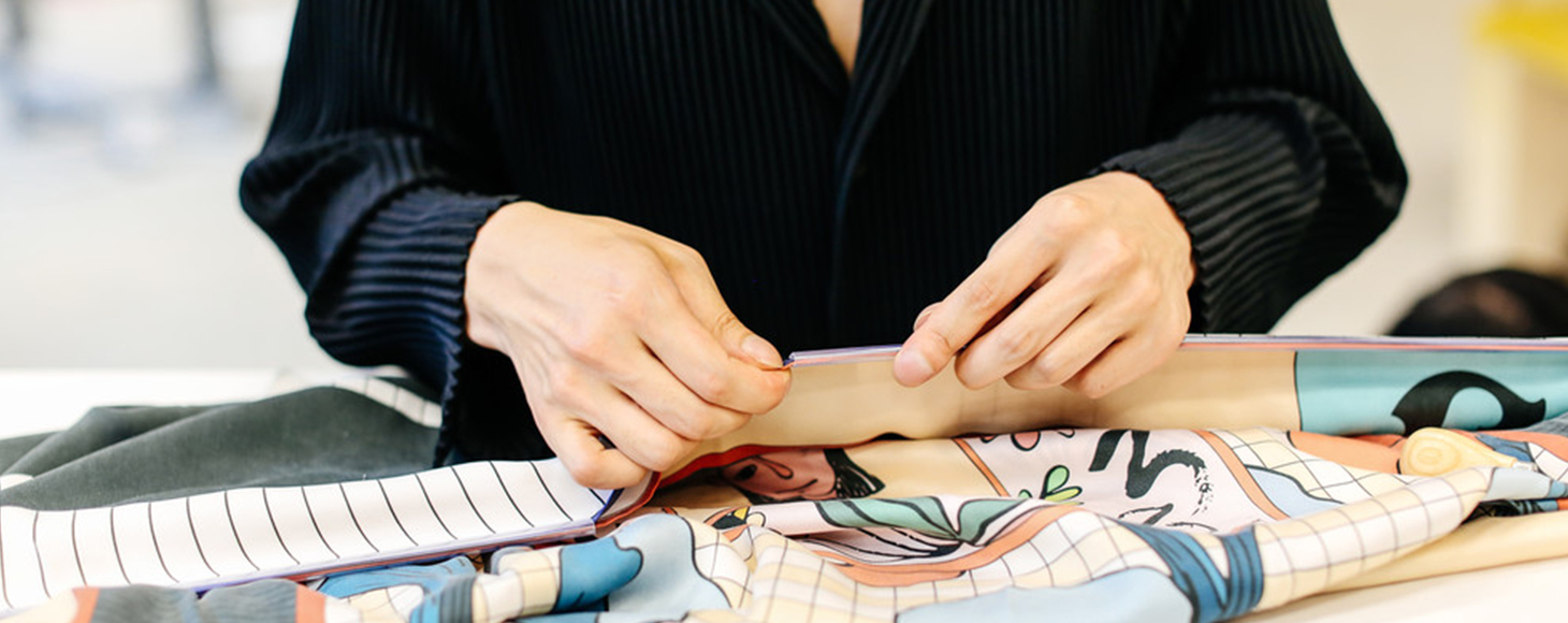 A female designer working with printed satin textile