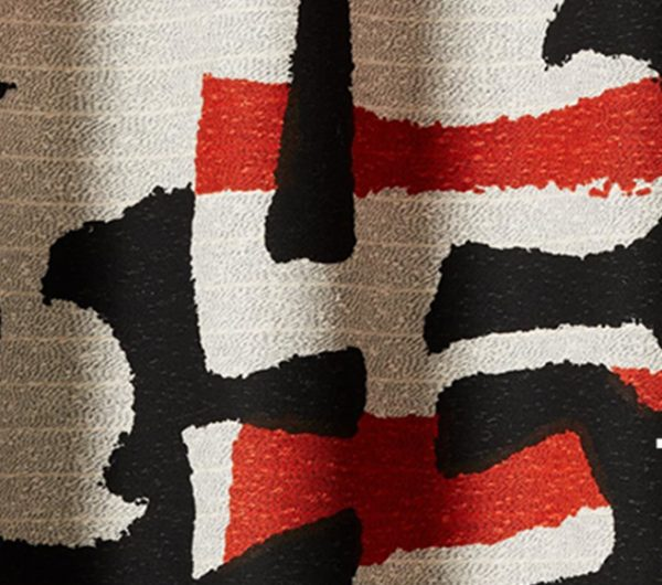 A hane-woven fabric by textile weaving compnay named Tibor. The fabic has red, black and off white yarns woven