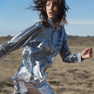 A model is wearing a metalic silver shirt and trousers with a desert in background