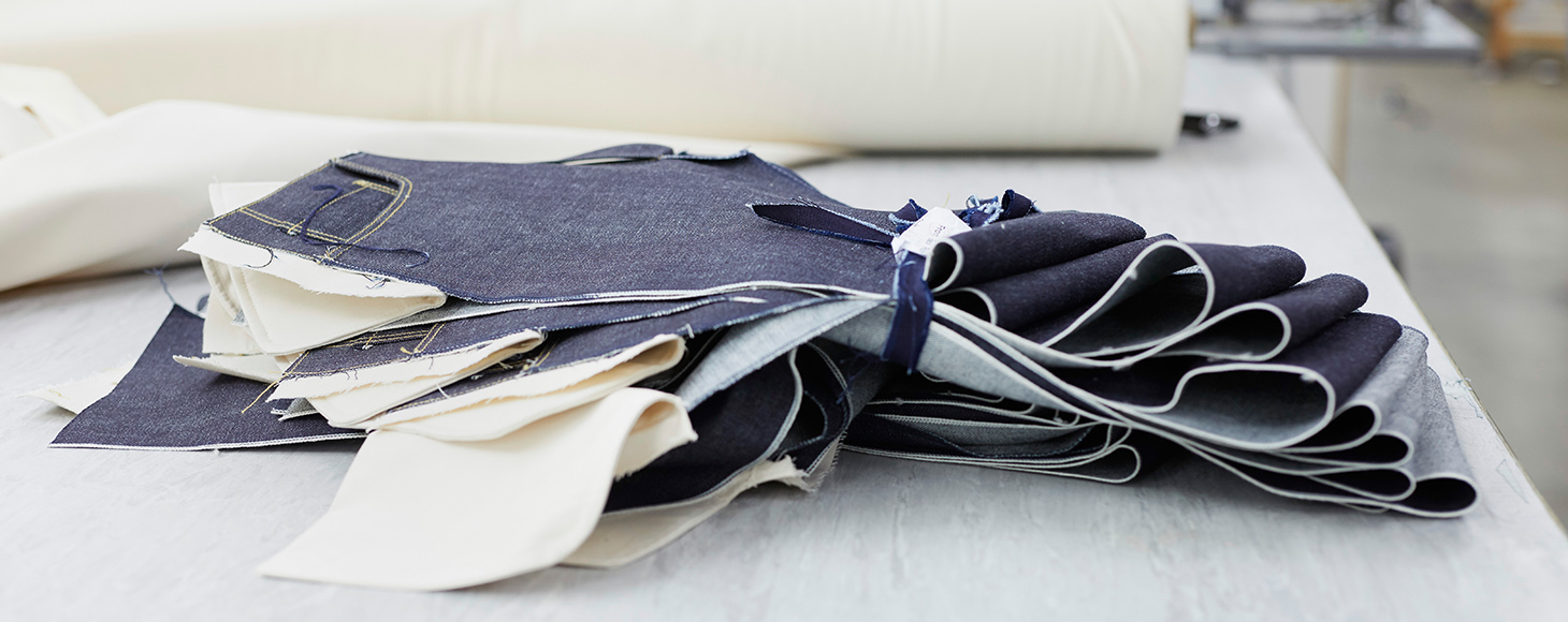 A collection of cut denim to the size is shown on a desk in a studio