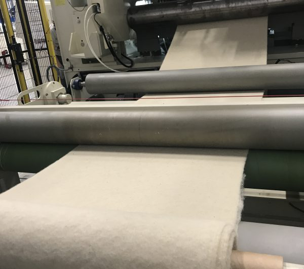 Fabric is being rolled out of a machine