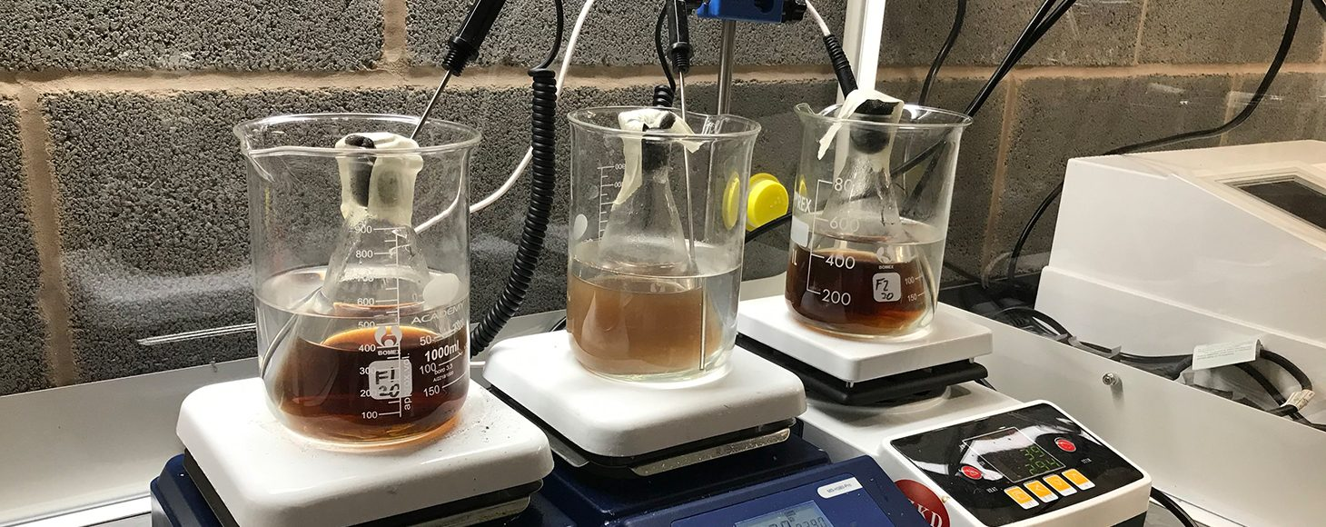 Three glass jars with brown liquid for experimental research